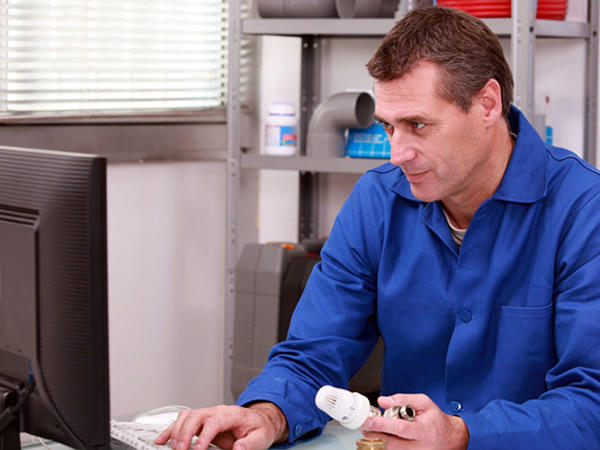 A plumber sitting at a computer taking an order